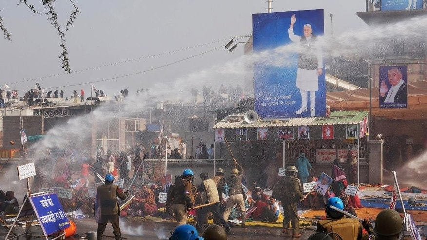 Indian police use batons and water cannon to disperse supporters, as they storm the ashram of controversial Indian guru Sant Rampal, at Hisar in Haryana state, India, Tuesday, Nov.18, 2014. Several people were injured in the incident. Rampal, had repeatedly ignored court summons to appear for questioning in the 2006 killing of a villager by his supporters. The supporters had formed a human chain around the ashram in an attempt to prevent police from entering. (AP Photo/ Bansilal Basniwal)