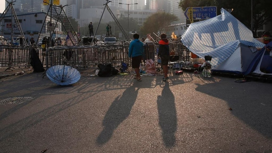 Pro-democracy protesters stand at an occupied area before barricades are removed outside government headquarters in Hong Kong's Admiralty district Tuesday, Nov. 18, 2014. Workers in Hong Kong on Tuesday started clearing away barricades at one site of the student protest that has rocked the city for the last two months. The removal came after a Hong Kong court granted a restraining order against the protesters last week requiring them to clear the area in front of a tower in the central part of Hong Kong as well a separate order against a second protest site Mong Kok brought by taxi and minibus operators. (AP Photo/Kin Cheung)