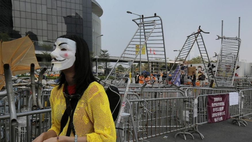 A pro-democracy protester wearing a mask waits at an occupied area before barricades are removed by workers outside government headquarters in Hong Kong Tuesday, Nov. 18, 2014. Workers in Hong Kong on Tuesday started clearing away barricades at one site of the student protest that has rocked the city for the last two months. The removal comes after a Hong Kong court granted a restraining order against the protesters last week requiring them to clear the area in front of a tower in the central part of Hong Kong as well a separate order against a second protest site Mong Kok brought by taxi and minibus operators. (AP Photo/Vincent Yu)