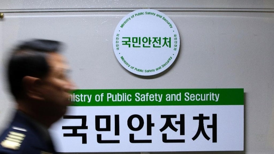 A government official walks by a signboard of newly created Ministry of Public Safety and Security at government complex in Seoul, South Korea, Wednesday, Nov. 19, 2014. South Korea's President Park Geun-hye on Tuesday nominated a retired navy general as head of the new broader safety agency to be created in the aftermath of April's ferry sinking that killed more than 300 people. (AP Photo/Lee Jin-man)