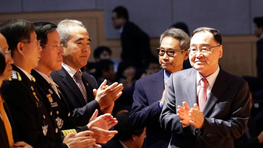 South Korean Prime Minister Chung Hong-won, right, applauds with government officials during an inauguration ceremony of the newly created Ministry of Public Safety and Security at government complex in Seoul, South Korea, Wednesday, Nov. 19, 2014. South Korea's President Park Geun-hye on Tuesday nominated a retired navy general as head of the new broader safety agency to be created in the aftermath of April's ferry sinking that killed more than 300 people. (AP Photo/Lee Jin-man)