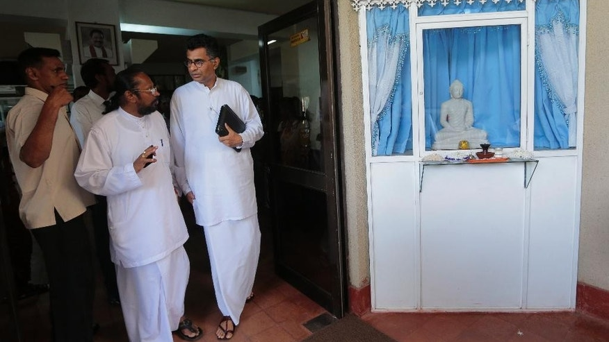 Sri Lankan Technology and Research Minister Champika Ranawaka, right, talks to an unidentified person as he leaves after a press conference, in Colombo, Sri Lanka, Tuesday, Nov. 18, 2014. Ranawaka, who represents the National Sinhala Heritage party, resigned Tuesday from the Cabinet after Sri Lankan President Mahinda Rajapaksa refused to agree to the party's 35 demands, including making him answerable to Parliament and the courts. (AP Photo/Eranga Jayawardena)