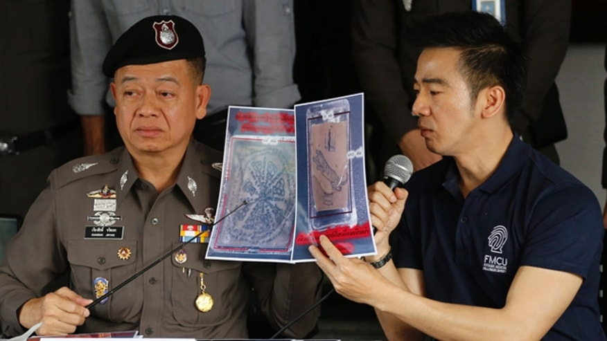 November 17, 2014: Thai police officers show pictures of a tattooed human skin during a press conference at Bangpongpang police station in Bangkok. (AP Photo/Sakchai Lalit)