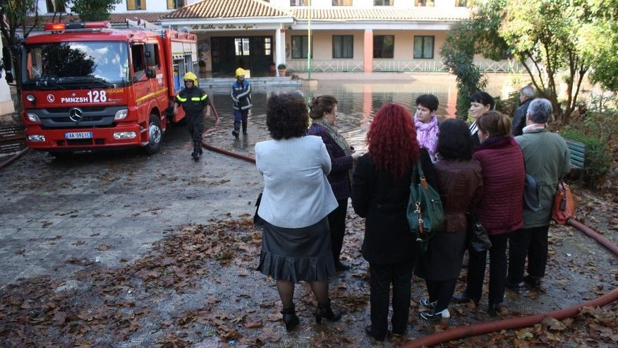 Teachers watch firefighters as they try to take out water from an elementary school in Tirana on Wednesday, Nov. 19, 2014. Flooding in Albania has killed three people, after torrential rain caused power and water supply cuts in the western part of the country, authorities said Wednesday. (AP Photo)