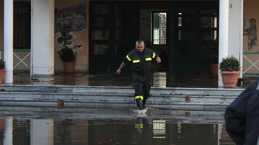 A firefighter walks in flood water as he  tries to take out water from an elementary school in Tirana on Wednesday, Nov. 19, 2014. Flooding in Albania has killed three people, after torrential rain caused power and water supply cuts in the western part of the country, authorities said Wednesday. (AP Photo)