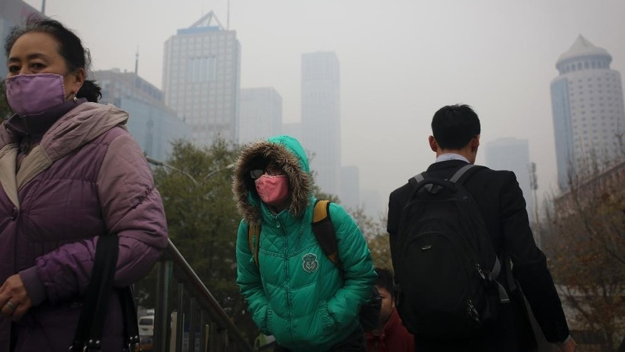 People wearing masks to protect themselves from pollutants walk on a pedestrian overhead bridge as city skylines are shrouded with haze in Beijing Wednesday, Nov. 19, 2014. During APEC summit In China, U.S. President Barack Obama set an ambitious target for cutting U.S. emissions in a landmark deal in which China will also rein in its emissions. In Australia G20 summit, he pledged $3 billion to help poorer nations address changing temperatures. (AP Photo/Andy Wong)
