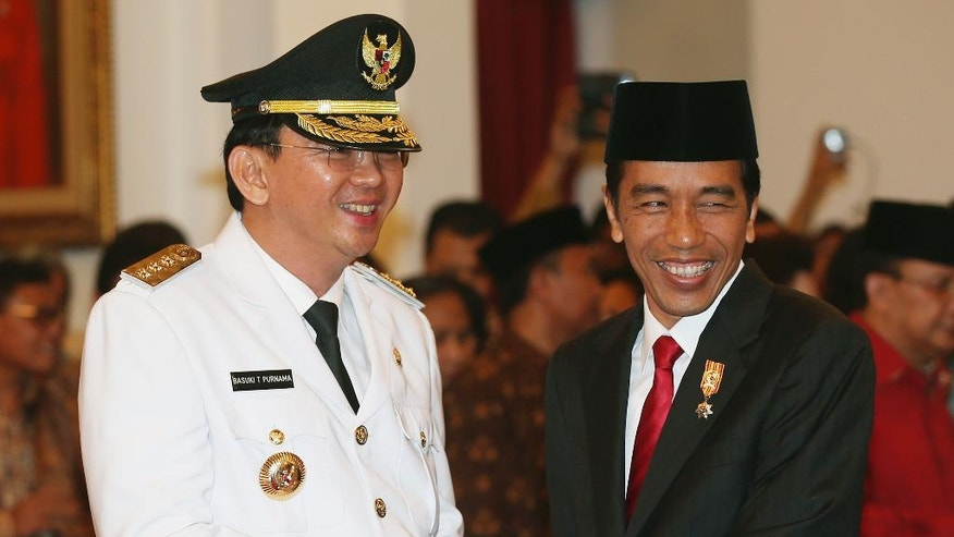 Basuki Tjahaja Purnama, left, is congratulated by Indonesian President Joko Widodo after taking the oath of office to become the governor of Indonesia's capital Jakarta, Wednesday, Nov. 19, 2014. Purnama, a Christian, was sworn in despite protests from Islamic hardliners who insist the job should be reserved for a Muslim in the city of 12 million people. (AP Photo/Tatan Syuflana)