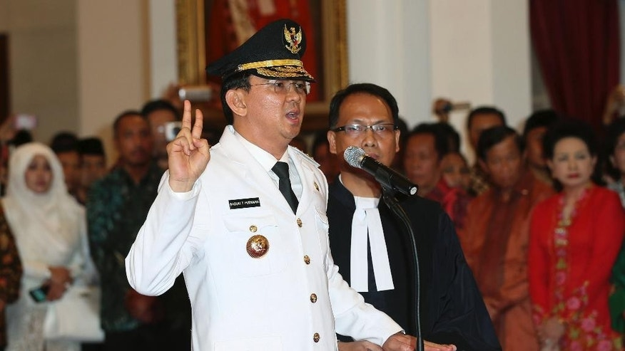 Basuki Tjahaja Purnama takes the oath of office to become the governor of Indonesia's capital Jakarta, Wednesday, Nov. 19, 2014. Purnama, a Christian, was sworn in despite protests from Islamic hardliners who insist the job should be reserved for a Muslim in the city of 12 million people. (AP Photo/Tatan Syuflana)