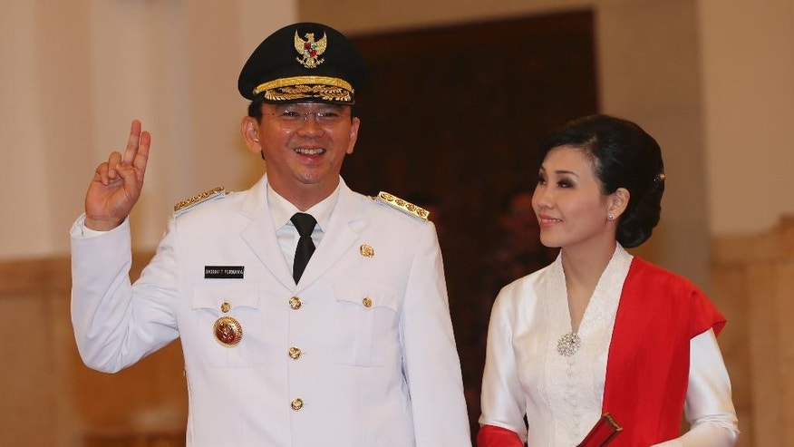 Basuki Tjahaja Purnama with his wife Veronica Tan poses prior to taking the oath of office to become the governor of Indonesia's capital Jakarta, Wednesday, Nov. 19, 2014. Purnam, a Christian, was sworn in despite protests from Islamic hardliners who insist the job should be reserved for a Muslim in the city of 12 million people. (AP Photo/Tatan Syuflana)