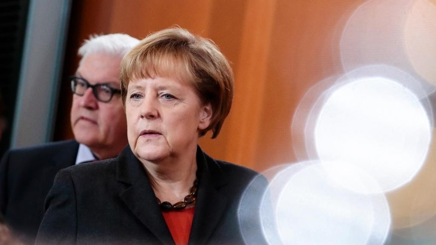 German Chancellor Angela Merkel, right, and Foreign Minister Frank Walter Steinmeier arrive for the weekly cabinet meeting at the chancellery in Berlin, Germany, Wednesday, Nov. 19, 2014. The reflections on the right site are from metal coffee cans on the cabinet desk. (AP Photo/Markus Schreiber)