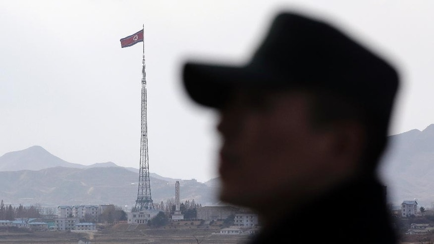 In this Wednesday, Nov. 12, 2014 photo, a South Korean soldier stands as a North Korean flag flutters in the wind atop a 160-meter (533-foot) tower in the village of Gijungdong, near the North side of the border village of Panmunjom, which has separated the two Koreas since the Korean War, north of Seoul, South Korea. North Korea threatened Thursday, Nov. 20, 2014 to bolster its war capability and conduct a fourth nuclear test to cope with what it calls U.S. hostility that led to the approval of a landmark U.N. resolution on its human rights violations. (AP Photo/Lee Jin-man)