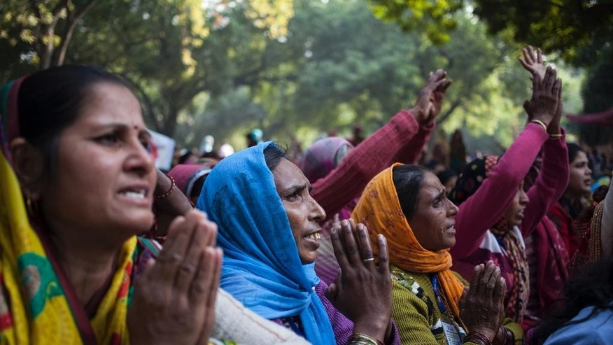 Supporters of controversial Indian guru Sant Rampal pray as they gather to show support at a protest venue near the Indian Parliament in New Delhi, India, Tuesday, Nov. 18, 2014. In the neighboring Haryana state's Hisar district, several supporters were injured on Tuesday after police searching for Rampal stormed an ashram where he was believed to be holed up. The guru, had repeatedly ignored court summons to appear for questioning in the 2006 killing of a villager by his supporters. (AP Photo/Tsering Topgyal)