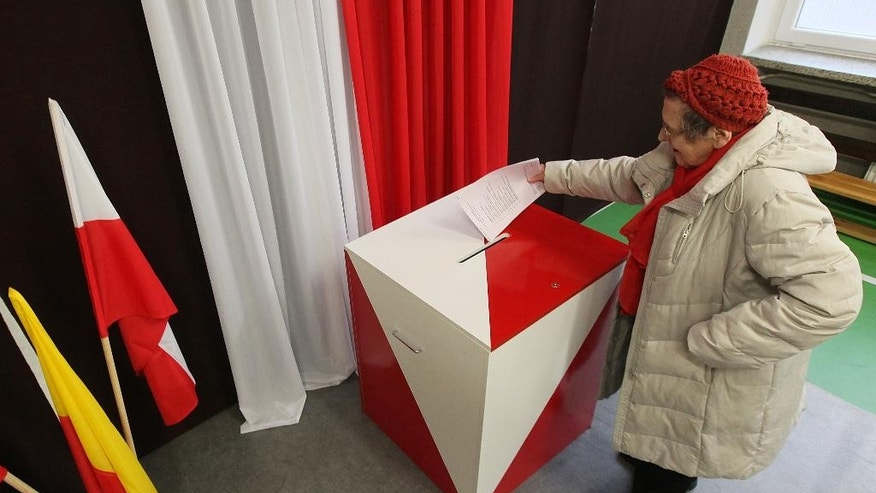 A woman casts her  ballot during the first round of Polish local elections, in Warsaw, Poland, Sunday, Nov. 16, 2014.  The voting is considered a test for the main parties ahead of the parliamentary elections next year. Some 30 million voters are eligible to choose nearly 47,000 councilors and 2,500 local administration leaders on Sunday, but observers are concerned about the possibility of a low turnout. Opinion polls gave a narrow lead to the governing pro-business Civic Platform party, over the nationalist opposition Law and Justice. (AP Photo/Czarek Sokolowski)