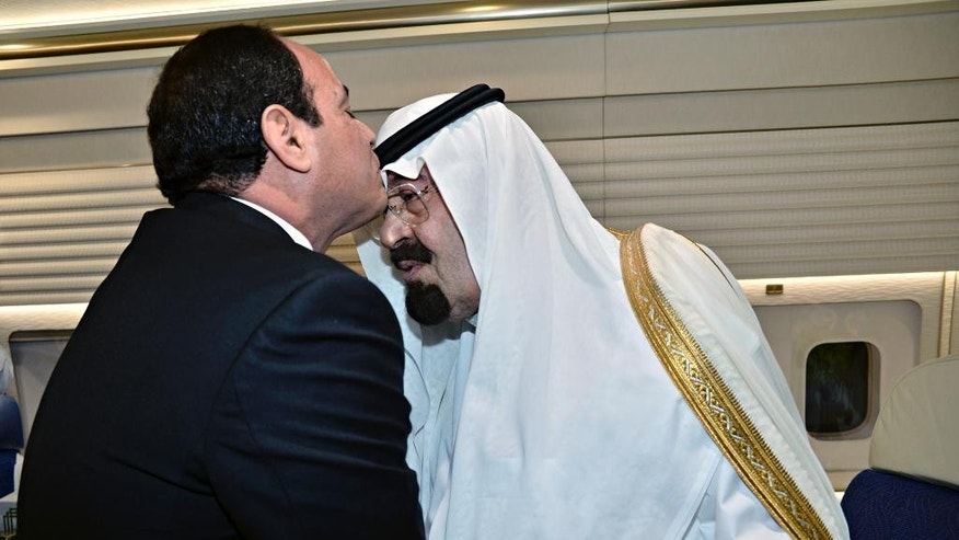 FILE - In this Friday, June 20, 2014 file photo provided by the Saudi Press Agency, Egyptian President Abdel-Fattah el-Sissi, left, kisses Saudi Arabia's King Abdullah, inside the king's airplane while parked at the Cairo International Airport in Egypt. King Abdullah on Wednesday, Nov. 19, 2014 called on regional ally Egypt to back a reconciliation agreement reached between Gulf states and Qatar following months of tensions linked to last year's military overthrow of Egyptian President Mohammed Morsi. The diplomatic spat was spurred by Qatar's support for Islamist movements across the region, particularly Egypt's Muslim Brotherhood group. (AP Photo/SPA, File)