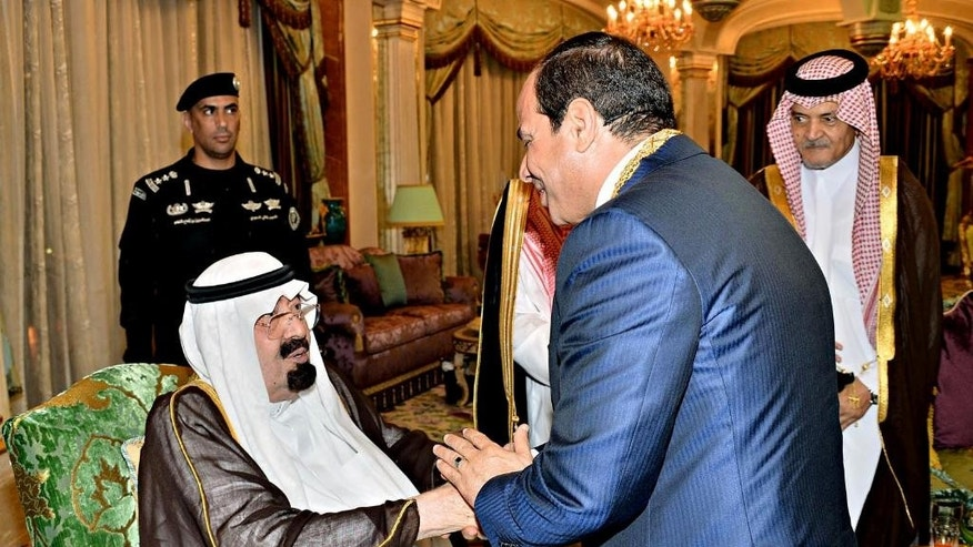 FILE - In this Sunday Aug. 10, 2014 file photo provided by Saudi Press Agency, Saudi's King Abdullah, left, shakes hands with Egyptian President Abdel-Fattah el-Sissi, after honoring him with a high medal, in Jiddah, Saudi Arabia. King Abdullah on Wednesday, Nov. 19, 2014 called on regional ally Egypt to back a reconciliation agreement reached between Gulf states and Qatar following months of tensions linked to last year's military overthrow of Egyptian President Mohammed Morsi. The diplomatic spat was spurred by Qatar's support for Islamist movements across the region, particularly Egypt's Muslim Brotherhood group. (AP Photo/Saudi Press Agency, File)