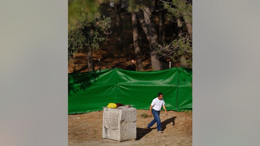 FILE - In this Oct. 19, 2009 file photo, a worker walks past a monolith memorial of Spanish poet Federico Garcia Lorca where it is believed he is buried in Alfacar, near Granada, southern Spain. Monday, Oct. 19, 2009. A search for unmarked Spanish Civil War graves has begun in Alfacar, southern Spain near where the acclaimed poet Federico Garcia Lorca is believed to have been executed and buried at the start of the conflict in 1936. Lorca, one of Spain's most renowned 20th-century poets, was among tens of thousands of civilians executed by right-wing militias and buried in unmarked mass graves during and after the 1936-1939 war. (AP Photo/Sergio Torres, File)
