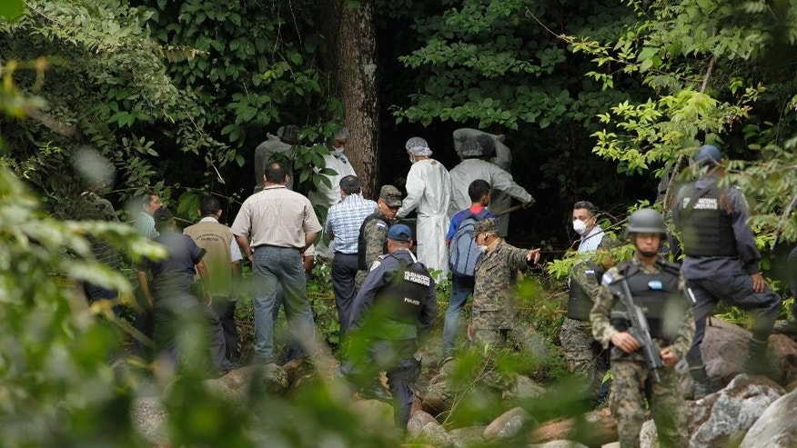 Police and forensic workers inspect the site where two bodies were found in the village of Cablotales, near Santa Barbara, Honduras, Wednesday, Nov. 19, 2014. The bodies, believed to belong to Miss Honduras 2014 and her sister, were found buried near the spa where they disappeared six days ago, according to the Honduras National Police Director Gen. Ramon Sabillon. Authorities were awaiting confirmation from forensic officials that the victims are Maria Jose Alvarado, 19, and her sister, Sofia, 23. (AP Photo)