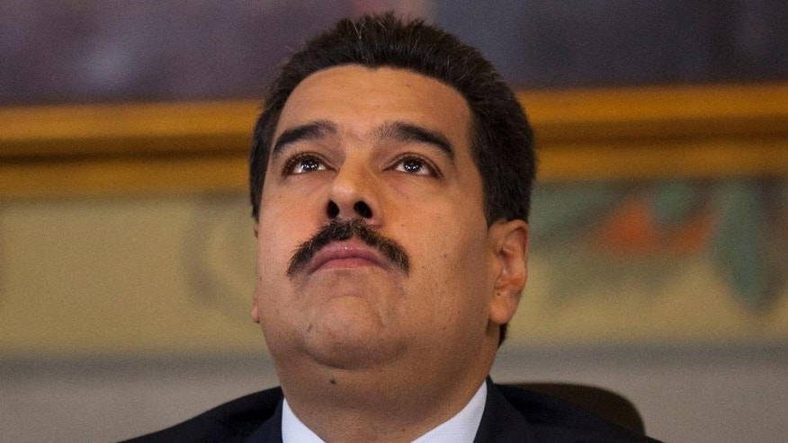 FILE - In this Oct. 15, 2014 file photo, Venezuela's President Nicolas Maduro looks up, minutes before the start of a press conference at Miraflores presidential palace in Caracas, Venezuela. Maduro used decree powers Tuesday, Nov. 18, 2014, to put in place 28 new measures, including a luxury tax, increased protection for young workers, and the establishment of new economic development zones. (AP Photo/Ariana Cubillos, File)