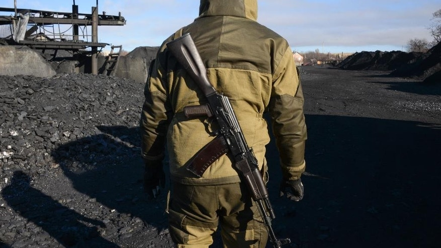 A pro-Russian rebel patrols an illegal coal mining warehouse in Torez, eastern Ukraine, Thursday, Nov. 20, 2014.  As battle raged in rebellion-wracked eastern Ukraine, cargo trains piled high with coal thundered along rail tracks to keep heating and power going to households in rebel-held territory. Coal is the lifeblood of this region dominated by pro-Russian separatists _ and now the source of its first corruption scandal.(AP Photo/Mstyslav Chernov)