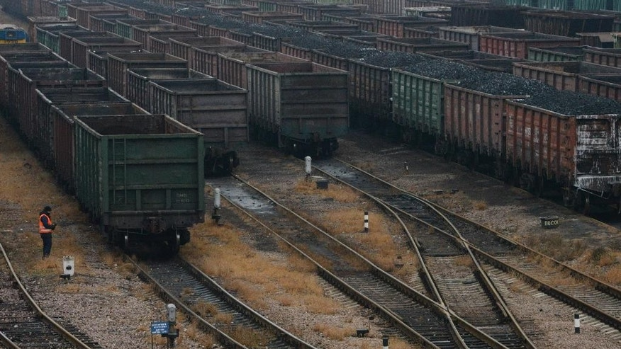 In this photo taken Wednesday, Nov. 19, 2014, wagons for transporting coal wait to be transferred in Donetsk, eastern Ukraine. As battle raged in rebellion-wracked eastern Ukraine, cargo trains piled high with coal thundered along rail tracks to keep heating and power going to households in rebel-held territory. Coal is the lifeblood of this region dominated by pro-Russian separatists _ and now the source of its first corruption scandal.(AP Photo/Mstyslav Chernov)