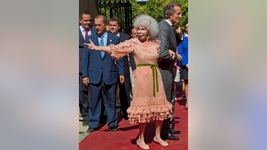 FILE - In this Oct. 5, 2011 file photo, Maria del Rosario Cayetana Alfonsa Victoria Eugenia Francisca Fitz-James Stuart y de Silva, Spanish Duchess of Alba, reacts as she walks out of the chapel with her husband Alfonso Diez after their wedding at Las Duenas Palace in Seville, Spain.The Duchess of Alba, one of Spain's wealthiest and most colorful aristocrats and listed as the world's most titled noble, has died at the age of 88. Maria del Rosario Cayetana Fitz-James Stuart y Silva died at her palatial home in the southern city of Seville on Thursday, Nov. 20, 2014. The cause of death was not immediately made known. A relative of Winston Churchill the duchess shared toys with England's future Queen Elizabeth II while living in England as a girl. (AP Photo/Miguel Angel Morenatti, File)