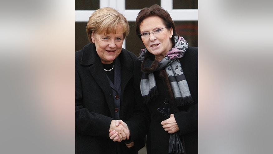 German Chancellor Angela Merkel, left, and Poland's Prime Minister Ewa Kopacz, right, shake hands before talks in Krzyzowa, Poland, on Thursday, Nov. 20, 2014, where they met  to mark 25 years since a symbolic reconciliation between Poland and Germany whose ties were marked by warfare in the past.  (AP Photo/Czarek Sokolowski)
