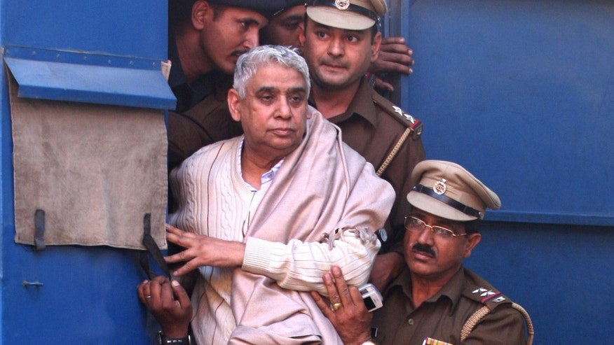 Nov. 20, 2014: Controversial religious leader Sant Rampal stands by the door of a police van as he is brought to a court, surrounded by police personnel in Chandigarh, India