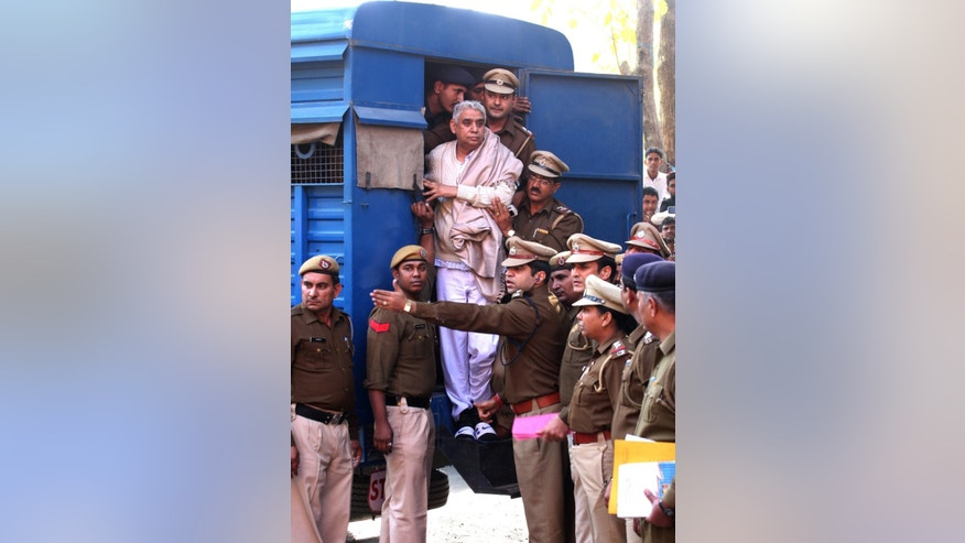 Controversial religious leader Sant Rampal stands by the door of a police van as he is brought to a court, surrounded by police personnel in Chandigarh, India, Thursday, Nov. 20, 2014. Indian police arrested the 63-year-old self-styled Hindu guru at his sprawling ashram in the northern part of the country, ending a days-long standoff in which six people died and hundreds were injured. He is wanted for questioning in a 2006 murder case, but has repeatedly ignored orders to appear in court. (AP Photo/Kapil Sethi)