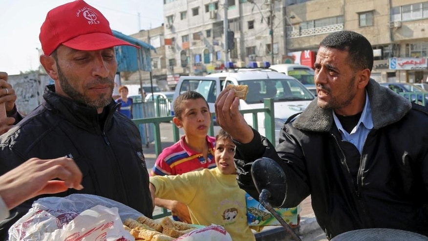 A Palestinian Hamas police officer receives sweets from a supporter of The Popular Front for the Liberation of Palestine, a small militant group, after they heard the news of a shooting attack in a Synagogue in Jerusalem, on a main road in Gaza City, northern Gaza Strip, Tuesday, Nov. 18, 2014. Two Palestinian cousins stormed a Jerusalem synagogue on Tuesday, attacking worshippers with meat cleavers and a gun during morning prayers and killing four people in the city's bloodiest attack in years. The attackers were killed in a shootout with police. (AP Photo/Adel Hana)