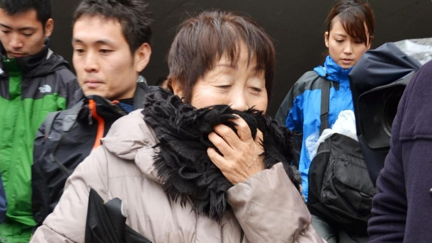 In this photo taken in March, Chisako Kakehi, center, answers to a reporter's question in Sakai, western Japan. Japanese police arrested the 67-year-old woman whom they suspect poisoned her husband late last year, one of about half a dozen former husbands or partners of the woman who have died. She has denied involvement in the deaths. Kyoto prefectural police arrested Kakehi on Wednesday, Nov. 19, 2014 after cyanide was found in the body of her 75-year-old husband, according to Japanese media reports. (AP Photo/Kyodo News) JAPAN OUT, MANDATORY CREDIT