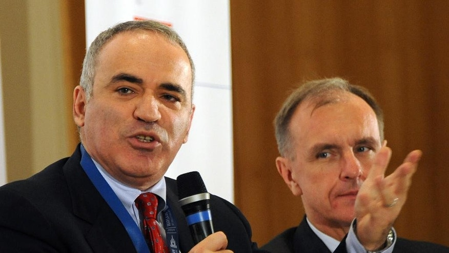 Russian chess master and political activist Garry Kasparov, left,  speaks at the Warsaw Security Forum, as Poland's former Defense Minister Bogdan Klich, right, listens, in Warsaw, Poland, Thursday, Nov. 20, 2014. Kasparov warned that if the west fails to stop Russia's President Vladimir Putin now the price for doing so could get much higher. (AP Photo/Alik Keplicz)