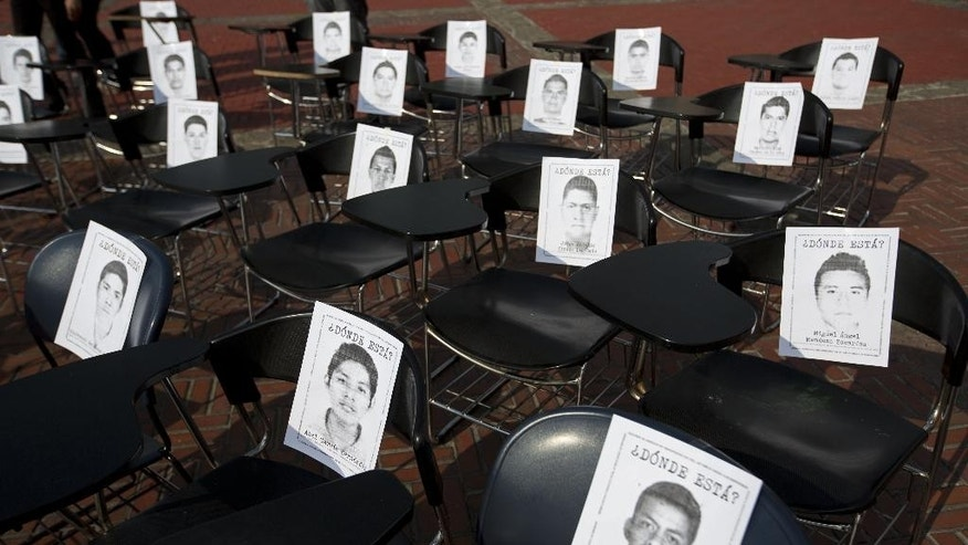 Photographs of the 43 disappeared students from the Rural Normal School of Ayotzinapa in the state of Guerrero sit on school desks placed in a plaza at Mexico's National Autonomous University (UNAM) as a form of protest by students in Mexico City, Thursday, Nov. 20, 2014. The students disappeared at the hands of a city police force on Sept. 26 in the town of Iguala. (AP Photo/Moises Castillo)