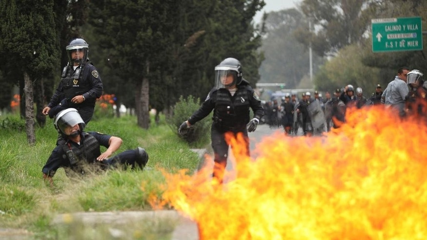 A riot police officer falls after protesters threw molotov cocktails at them near the airport in Mexico City,Thursday, Nov. 20, 2014. Mexico City is bracing for demonstrations as caravans of students and family members of 43 missing college students converged on the capital after several days crisscrossing the country. (AP Photo/Marco Ugarte)