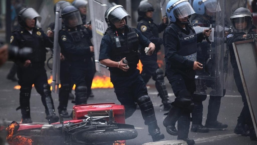 A riot police officer gathers rocks that were thrown at them as they move past a burning fast food delivery motorcycle after protesters threw molotov cocktails at them near the airport in Mexico City,Thursday, Nov. 20, 2014. Mexico City is bracing for demonstrations as caravans of students and family members of 43 missing college students converged on the capital after several days crisscrossing the country. (AP Photo/Marco Ugarte)