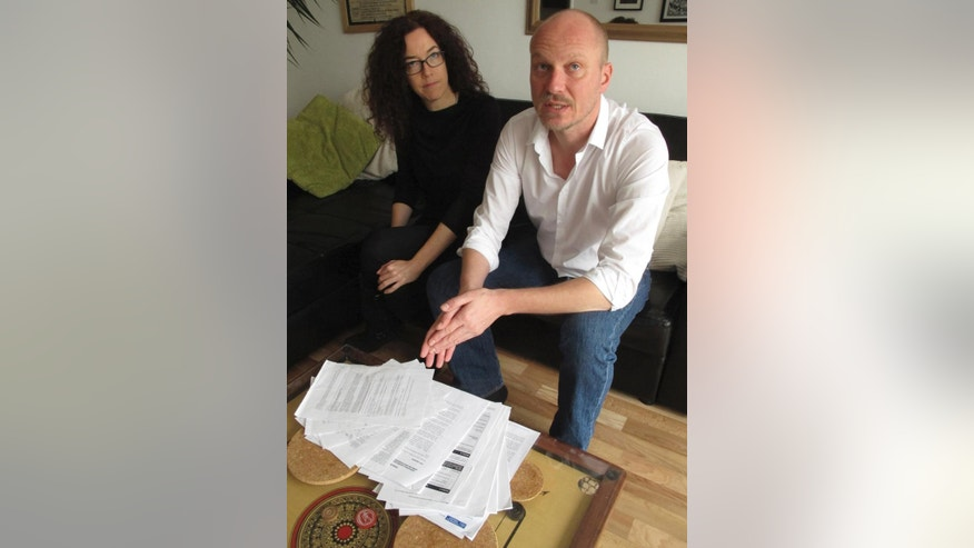 Freelance video journalist James Parkinson, 44, and freelance photographer Jess Hurd, 41, gesture at police surveillance files and other documents laid out on their living room table at their home in east London Friday Nov. 21, 2014. The pair are among six British journalists who are suing Londonís Metropolitan Police and Britainís Home Office over police surveillance of journalists' movements. (AP Photo/Raphael Satter)