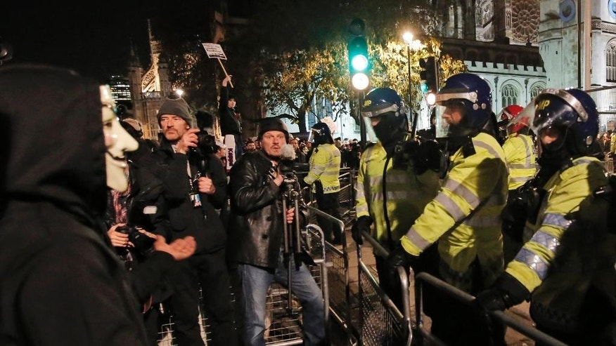 In this photo taken Wednesday, Nov. 7, 2014, freelance video journalist James Parkinson, center wearing a helmet and holding his camera on a tripod, films scuffles between British police officers, right, and anti-austerity demonstrators during a rally in central London. Parkinson, a 44-year-old freelancer who has covered hundreds of protests - some of them for The Associated Press - is among six British journalists who are suing London's Metropolitan Police and Britain's Home Office over police surveillance of journalists' movements. Parkinson, three photographers, an investigative journalist and a newspaper reporter are filing the lawsuit after obtaining their surveillance records. (AP Photo/Lefteris Pitarakis)