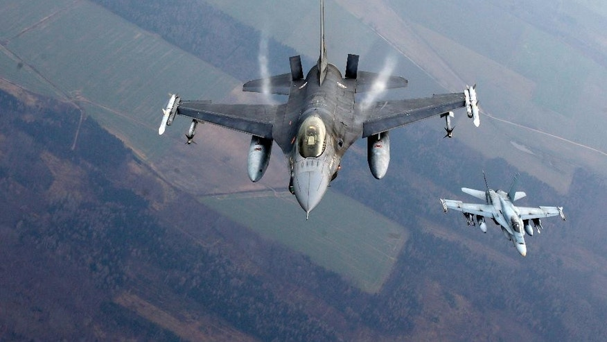 """A Portuguese military fighter jet, left, and a Canadian military fighter jet participating in NATO's Baltic Air Policing Mission operate in Lithuanian airspace, Thursday, Nov. 20, 2014. NATO, which has 16 fighter jets in the region monitoring Baltic airspace, said it regularly launches jets to identify """"unknown or potentially hostile aircraft"""" in the proximity of national airspace. (AP Photo/Mindaugas Kulbis)"""