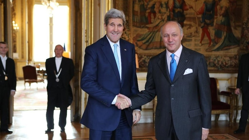 U.S. Secretary of State John Kerry, left, is greeted by French foreign minister Laurent Fabius prior to their meeting at the foreign ministry in Paris Thursday, Nov. 20, 2014. U.S. Secretary of State John Kerry is in Paris for talks with the French and Saudi foreign ministers as part of a last-minute push to secure a nuclear deal with Iran. (AP Photo/Remy de la Mauviniere, Pool)