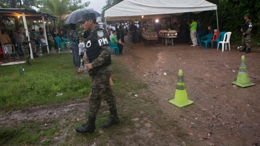 Military police provide security for the wake for slain beauty queen Maria Jose Alvarado, 19, and her sister Sofia, 23, as it rains in Santa Barbara, Honduras, Thursday, Nov. 20, 2014. Grieving family members laid to rest a Honduran beauty queen and her sister amid drenching rains Thursday, pleading for divine justice after the women were shot to death in what police say was a jealous rage by the sister's boyfriend. (AP Photo/Esteban Felix)