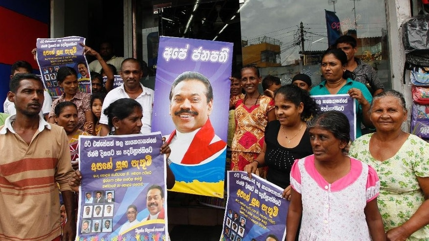"Supporters of Sri Lankan President Mahinda Rajapaksa hold posters and celebrate following a call for presidential election in Colombo, Sri Lanka, Thursday, Nov. 20, 2014. Rajapaksa has called an early election to seek a third term in office two years before his current term expires. He was first elected in 2005 and overwhelmingly won another six-year term in 2010, riding on his popularity for defeating Tamil Tiger rebels in a civil war that ended in 2009. He used his party's parliamentary victory in 2010 to scrap a two-term limit in office. Placard center reads ""Our President,"" and posters are felicitations on his birthday which was marked on Nov. 18.  (AP Photo/Eranga Jayawardena)"