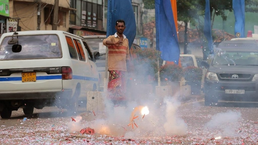 A supporter of Sri Lankan President Mahinda Rajapaksa bursts firecrackers following a call for presidential election in Colombo, Sri Lanka, Thursday, Nov. 20, 2014. Rajapaksa has called an early election to seek a third term in office two years before his current term expires. He was first elected in 2005 and overwhelmingly won another six-year term in 2010, riding on his popularity for defeating Tamil Tiger rebels in a civil war that ended in 2009. He used his party's parliamentary victory in 2010 to scrap a two-term limit in office. (AP Photo/Eranga Jayawardena)