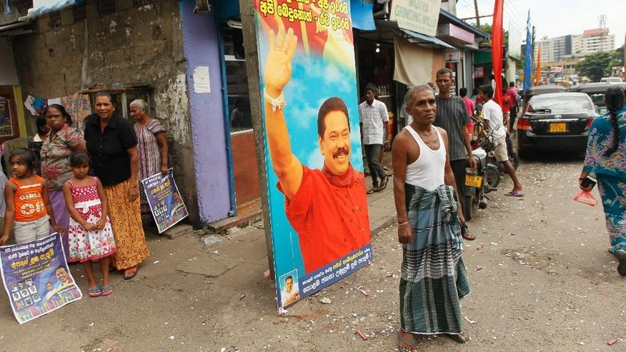 "Sri Lankans stand next to a giant billboard with a portrait of Sri Lankan President Mahinda Rajapaksa at a locality with majority Rajapaksa supporters, following a call for presidential election in Colombo, Sri Lanka, Thursday, Nov. 20, 2014. Rajapaksa has called an early election to seek a third term in office two years before his current term expires. Billboard reads ""Divided, there is no country. There is no country without the President."" (AP Photo/Eranga Jayawardena)"