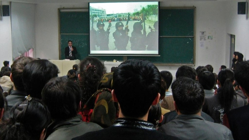 "FILE - In this Nov. 6, 2009 file photo, economist Ilham Tohti, left in the background, a professor from China's predominantly Muslim Xinjiang region, talks while showing a photo of heavily armed Chinese policemen facing off with a group of Uighur protesters during July 2009 ethnic violence, to students at the Central Nationalities or Minzu University in Beijing, China. Over two weeks in late 2014, the state-owned Liaoning Daily newspaper in China's northeast sent reporters to sit in on dozens of university lectures all over the country looking for what the paper said were professors ""being scornful of China."" Earlier in the year Tohti was even sentenced to life in prison on separatism charges in part for championing the rights of the country's Muslim Uighur minority during his lectures.(AP Photo/Alexa Olesen, File)"