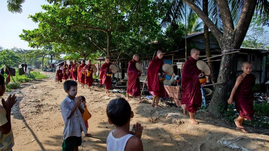 In this Nov. 19, 2014 photo, young children put their hands together as Buddhist monks walk past in Hlaing Tharyar, northwest of Yangon, Myanmar to collect morning alms. In its latest World Giving Index, the U.K.-based Charities Aid Foundation said Myanmar shared the top spot with the United States. The foundation ranked countries based on the percentage of people who said they had donated money, volunteered or helped strangers in the month before they were surveyed. It attributed Myanmar's giving to the charitable traditions of Theravada Buddhism. (AP Photo/Gemunu Amarasinghe)