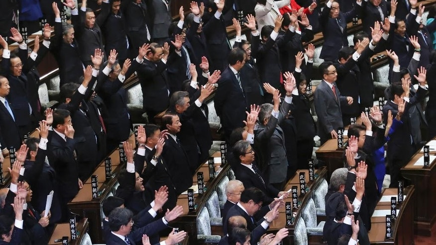 Lawmakers at the House of Representatives shout a banzai cheer after the lower house is dissolved in Tokyo, Friday, Nov. 21, 2014.  Prime Minister Shinzo Abe has dissolved the lower house of Japan's parliament, paving the way for a general election next month. Friday's dissolution will lead to elections expected on Dec. 14. (AP Photo/Koji Sasahara)