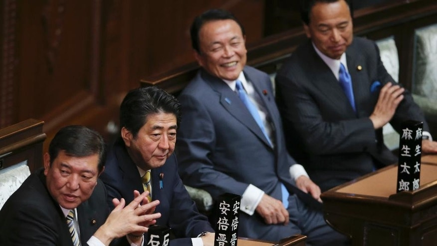 Japanese Prime Minister Shinzo Abe, second left, Minister in charge of regional issues Shigeru Ishiba, left, and Finance Minister Taro Aso, third left, attend a parliamentary session where the parliament was dissolved for a general election in Tokyo, Friday, Nov. 21, 2014.  Prime Minister Abe has dissolved the lower house of Japan's parliament, paving the way for a general election next month. Friday's dissolution will lead to elections expected on Dec. 14.(AP Photo/Koji Sasahara)