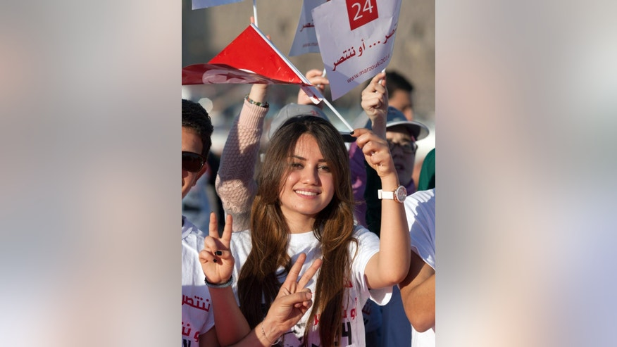 A supporter of presidential candidate and Tunisian President, Moncef Marzouki, waves her national flag during a campaign meeting in Bizerte, northern Tunisia, Wednesday, Nov. 19, 2014. The presidential campaign, featuring 25 competitors, kicked off in early November and it's the first time since Tunisians overthrew dictator Zine El Abidine Ben Ali in 2011 that they will choose their head of state through universal suffrage. If no candidate wins a majority Nov. 23, there will be a runoff between the top two vote-getters on Dec. 28. (AP Photo/Aimen Zine)