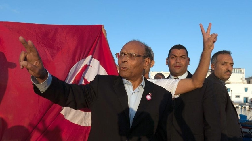 Presidential candidate and Tunisian President, Moncef Marzouki, waves before addressing his supporters during a campaign meeting in Bizerte, northern Tunisia, Wednesday, Nov. 19, 2014. The presidential campaign, featuring 25 competitors, kicked off in early November and it's the first time since Tunisians overthrew dictator Zine El Abidine Ben Ali in 2011 that they will choose their head of state through universal suffrage. If no candidate wins a majority Nov. 23, there will be a runoff between the top two vote-getters on Dec. 28. (AP Photo/Aimen Zine)