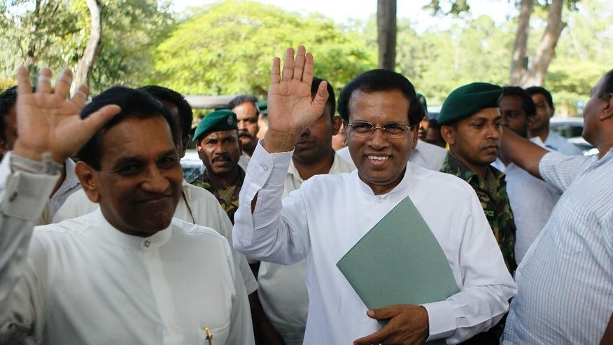 Sri Lankan Health Minister Maithripala Sirisena, right, and Fisheries Minister Rajitha Senaratne acknowledge the gathering as they arrive for a press briefing in Colombo, Sri Lanka, Friday, Nov. 21, 2014.  Sirisena quit President Mahinda Rajapaksa's government Friday to challenge him in the upcoming elections in the most serious setback for the leader's quest for a third term. Sirisena left the government with three other ministers, including Senaratne, and a lawmaker, saying Friday he has been chosen as the combined opposition's presidential candidate. (AP Photo/Eranga Jayawardena)