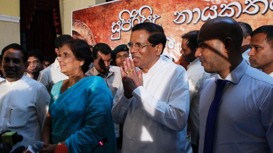 Sri Lankan Health Minister Maithripala Sirisena, center, acknowledges the gathering, with former Sri Lankan president Chandrika Kumaratunge standing by his right, at the end of a press conference in Colombo, Sri Lanka, Friday, Nov. 21, 2014. Sirisena quit President Mahinda Rajapaksa's government Friday to challenge him in the upcoming elections in the most serious setback for the leader's quest for a third term. Sirisena left the government with three other ministers and a lawmaker, saying Friday he has been chosen as the combined opposition's presidential candidate. (AP Photo/Eranga Jayawardena)